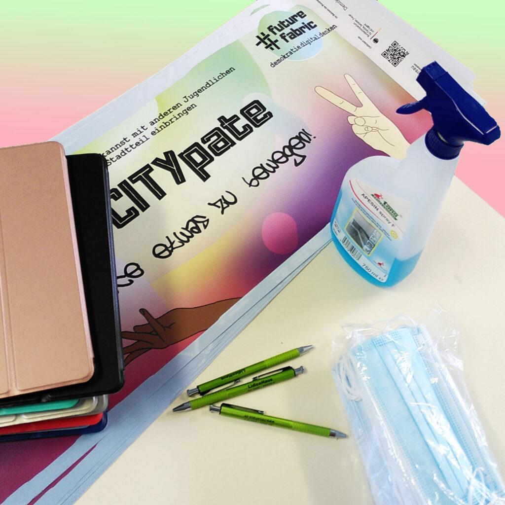 Symbolträchtige Gegenständes 1. Treffen Jugendjury auf einem Tisch: Plakat der Veranstaltung, Tablets, Mund-Nasen-Schutz, Stifte, Desinfektionsmittel